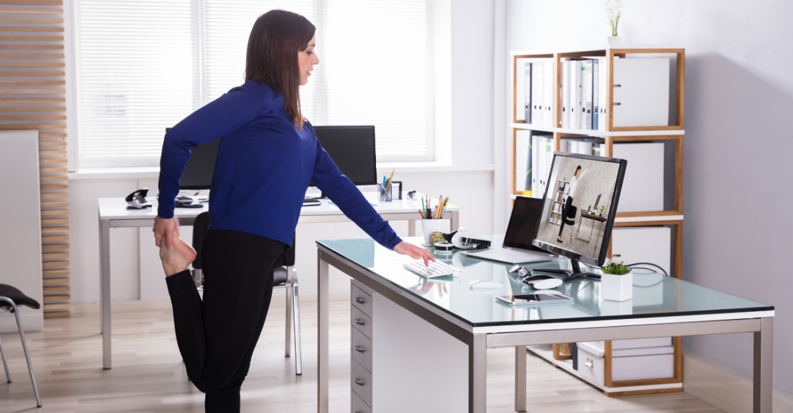 Woman stretching at her desk at work