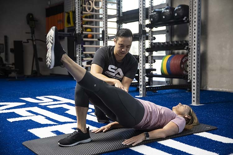 gym professional mobility trainer informing three client in hip extension exercise