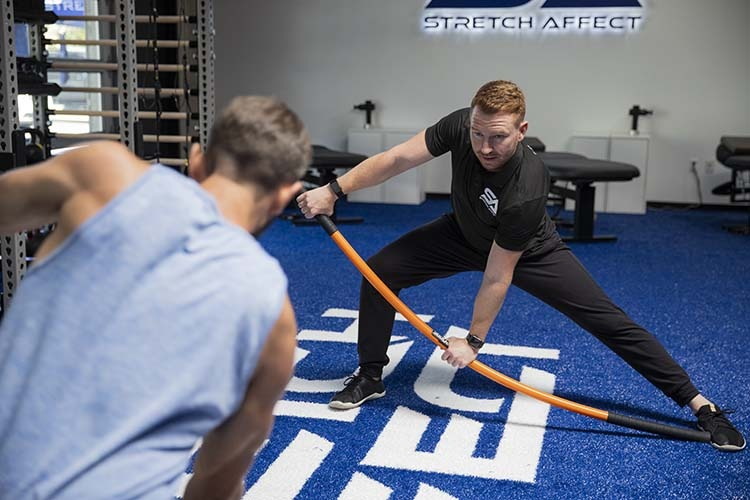 instructor demonstrates stick mobility exercise