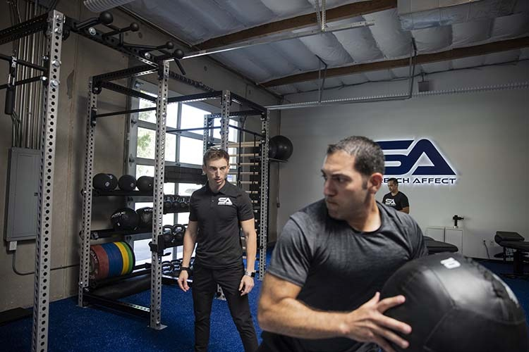 stretch professional monitors form of client in rotational medicine ball exercise