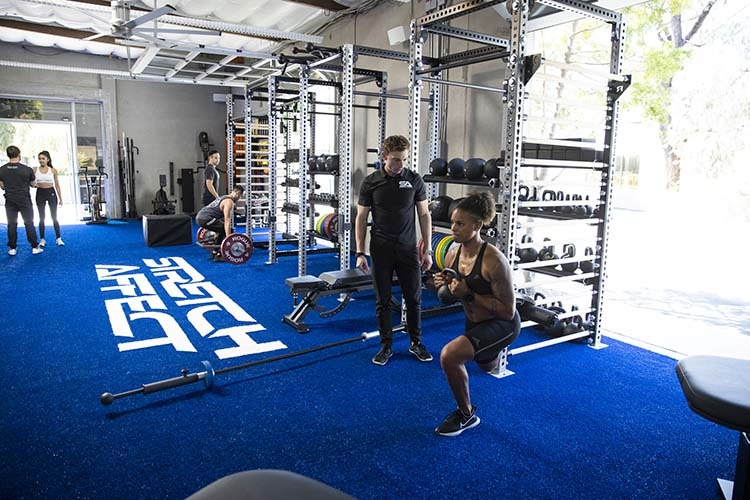gym with three professional trainers informing three clients in various exercises