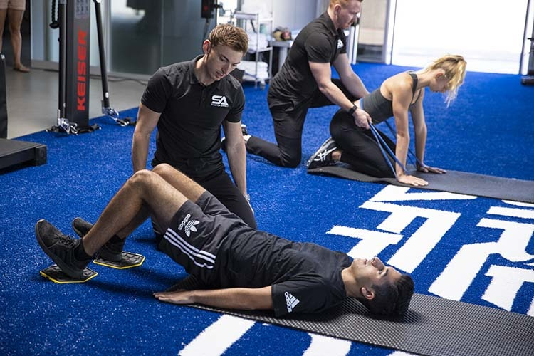 gym with two professional mobility trainers informing two clients in various exercises