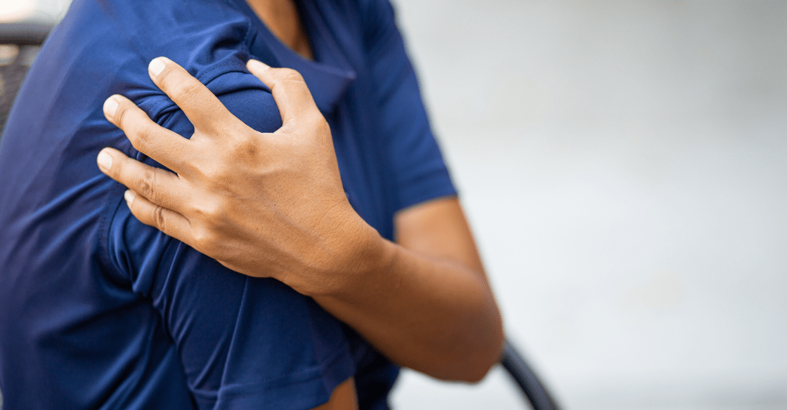 Young person in need of stretches for shoulder pain grabs shoulder in pain.