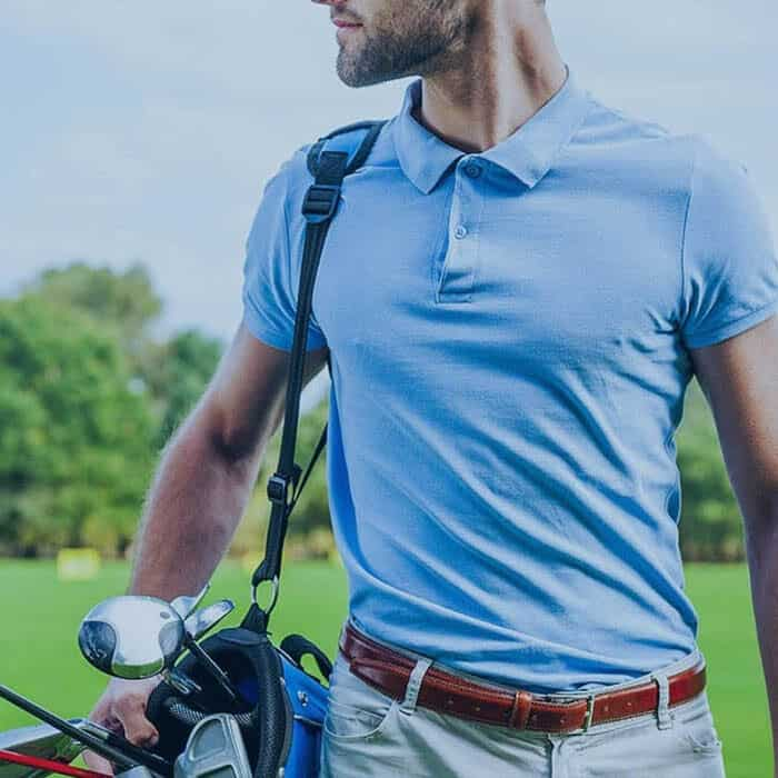 athletic man holding golf clubs on golf course