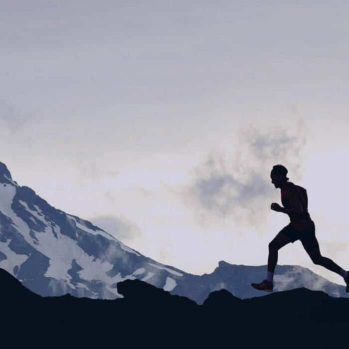 silhouette of man running by mountains