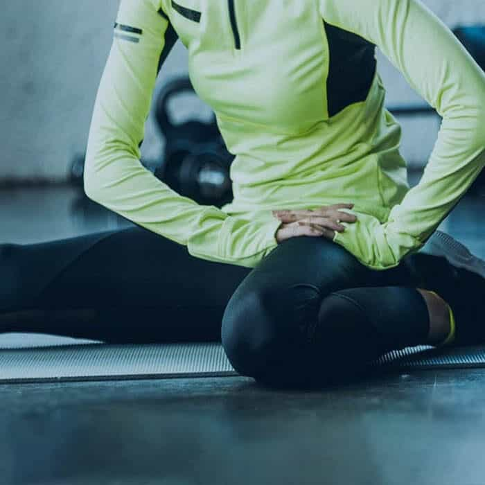 person in running attire performing seated hamstring stretch